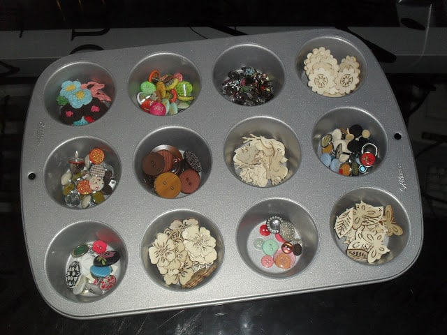 muffin tin that's being used to organize embellishments