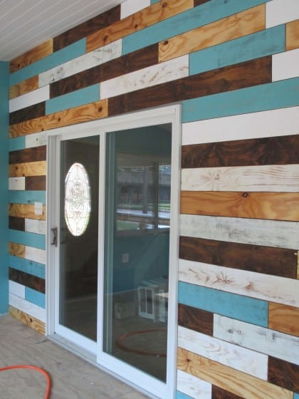 plank wall featuring multiple colors of paint and stain around a sliding glass door