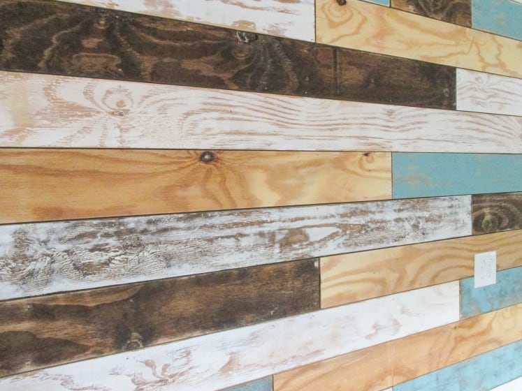 distressed wood planks in various colors nailed to the wall