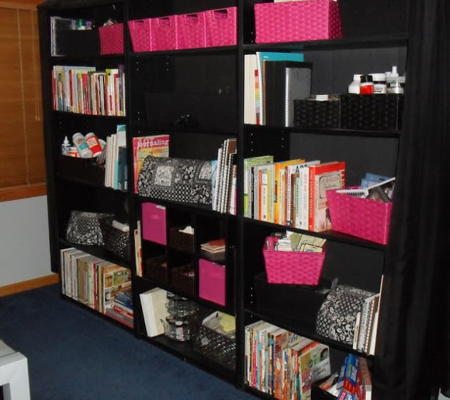 three black bookcases containing books and scrapbooking supplies organized in pink and black baskets