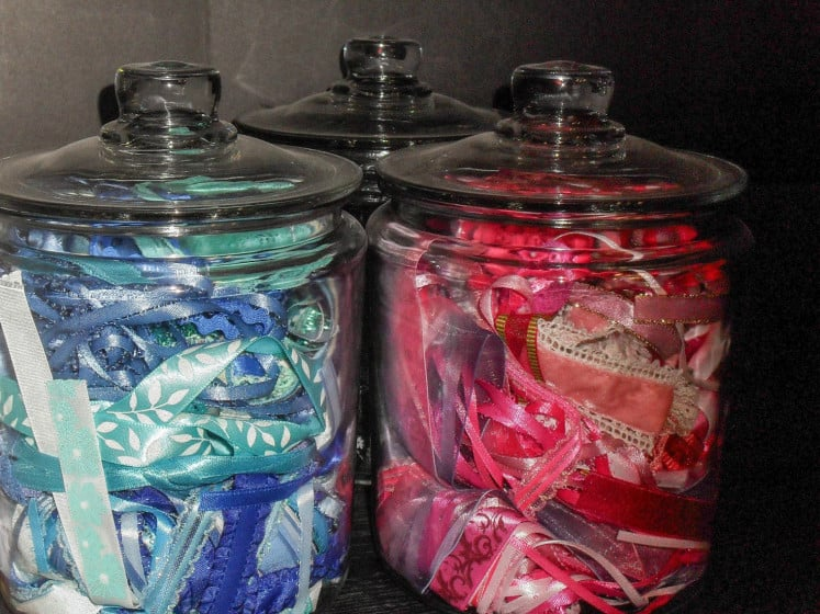 three glass jars filled with ribbon