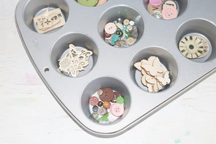 muffin tin filled with embellishments