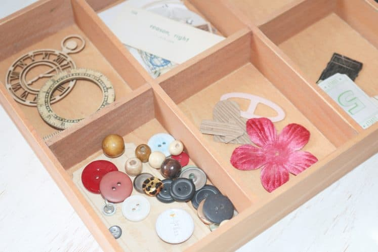 embellishments organized in wooden tray
