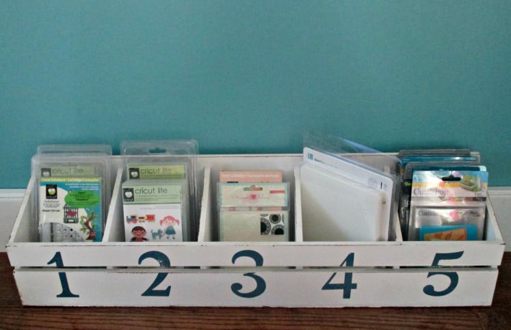 wooden organizer filled with Cricut cartridges and embossing folders