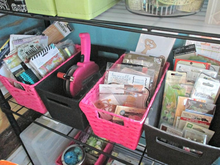 scrapbooking supplies organized into baskets on shelves