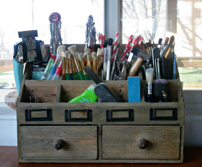 wooden desk organizer filled with paint brushes and other tools