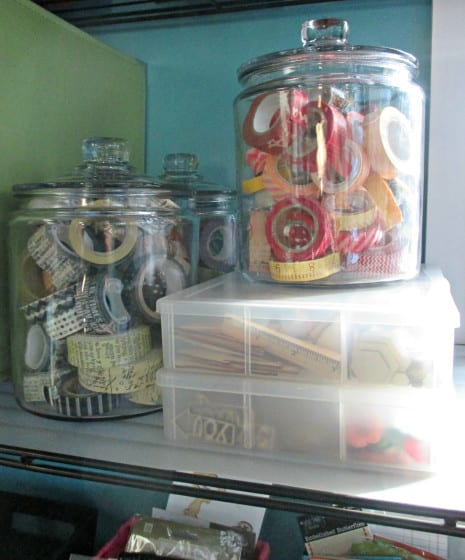 glass jars filled with washi tape and wood veneers organized into embroidery floss boxes
