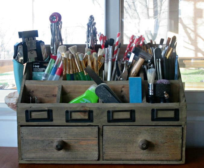desk organizer filled with paint brushes and other craft tools