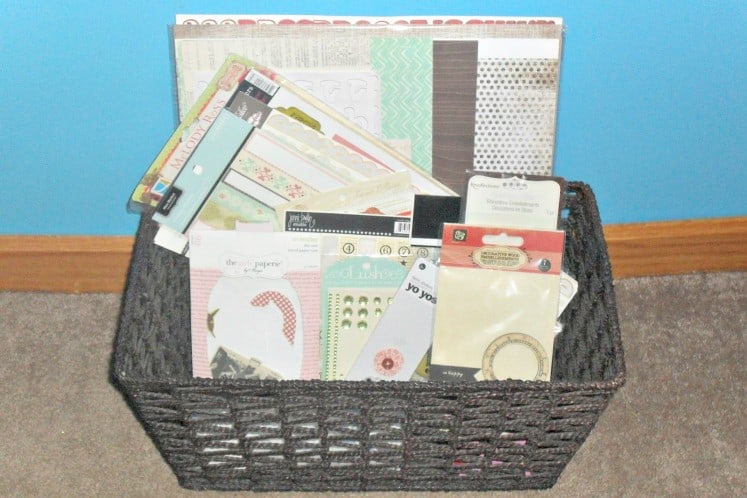 wicker basket filled with scrapbooking paper and embellishments
