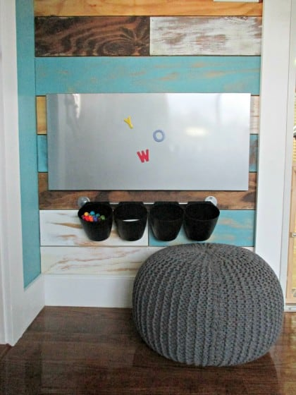 magnet board attached to wall with small cups hung from a metal rail beneath