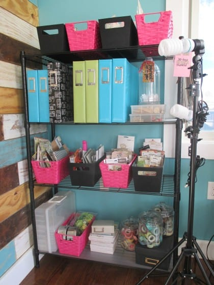 shelf filled with embellishments organized in containers and albums