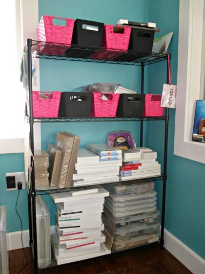 wire shelf with mixed media and art journaling supplies in baskets, chipboard, Project Life kits and canvases stacked neatly on shelves