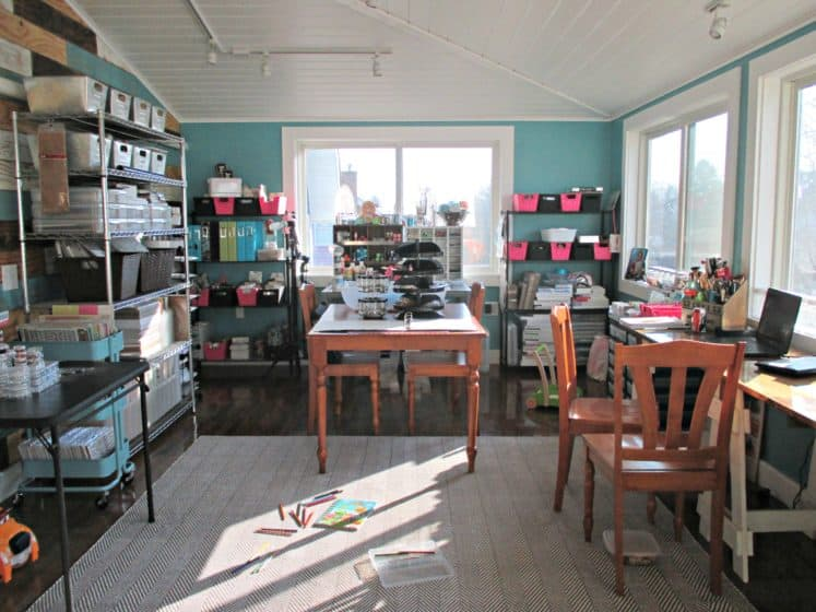craft room with several wire shelves filled with supplies as well as desks and tables