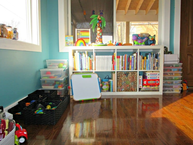child's play area with books and games organized on shelves and baskets of toys on the floor