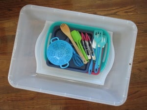 large clear bin filled with sensory materials and tools