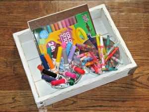 tray filled with children's art supples and spiral bound art journal