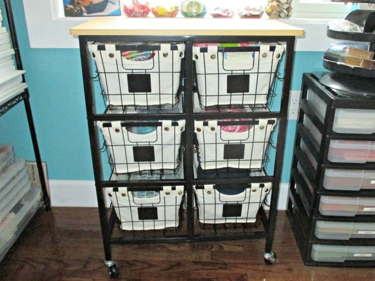 rolling cart with wire baskets full of sewing and quilting supplies