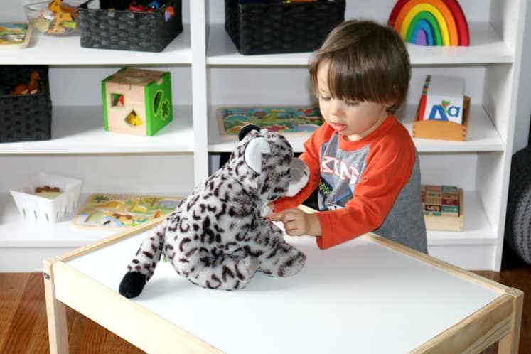 toddler boy pretending to be a veterinarian and examining a stuffed animal