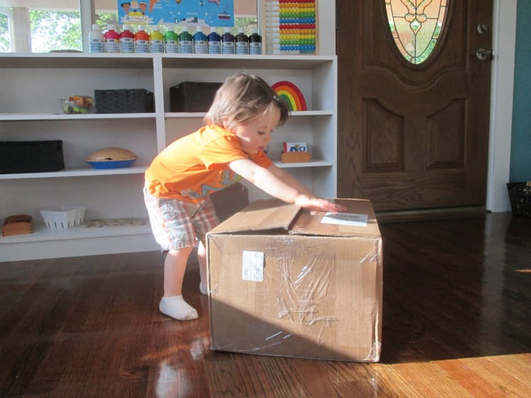 toddler opening large box of homeschool curriculum