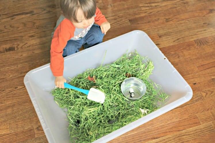 toddler exploring zoo babies sensory bin with a spatula