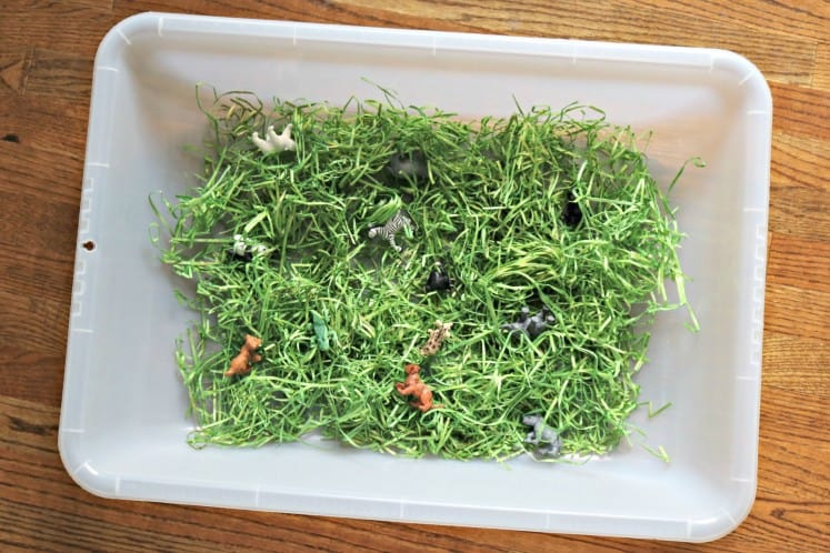 zoo baby scavenger hunt sensory bin made from pretend grass and small zoo animal manipulatives in a large clear bin