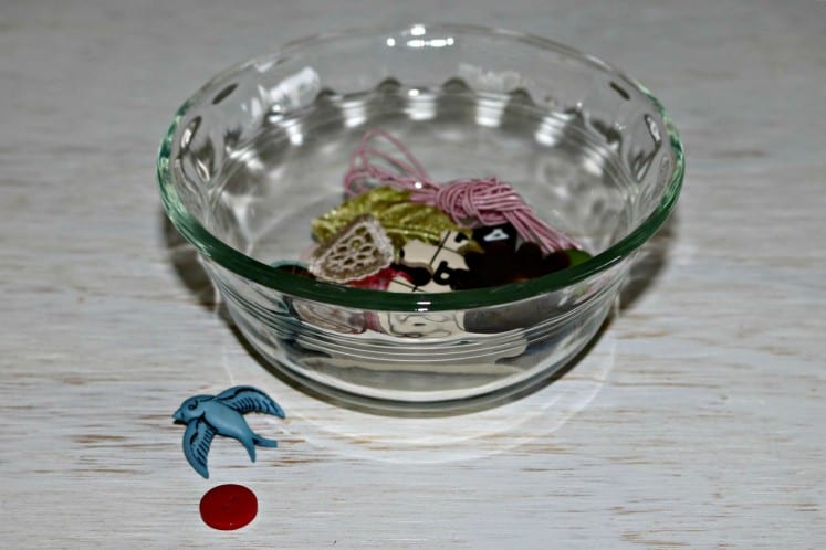 small embellishments in a glass dish with a few buttons scattered in front of it