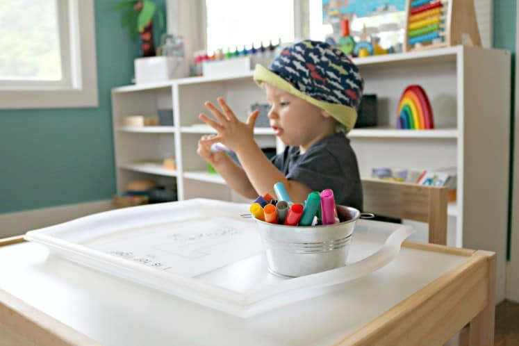 toddler boy sitting at a table putting the cap on a marker