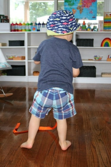 toddler pulling a piece of orange ribbon across the floor