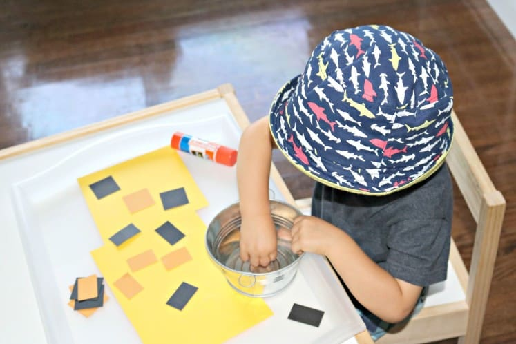 toddler working on tiger shape sort collage using orange and black rectangles and glue