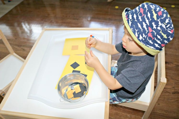 toddler boy creating a collage with orange and black rectangles