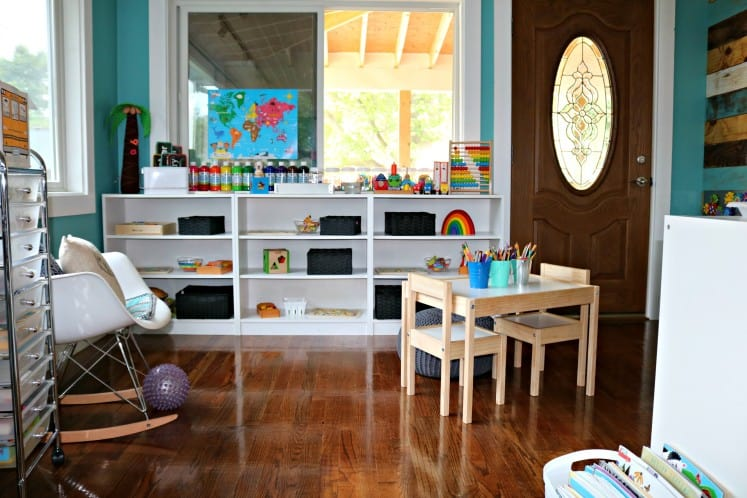 child's play area with neatly organized toys on shelves, rocking chair with pillows and table with buckets of art supplies