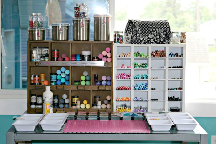 craft workspace with paints, inks, and markers in wooden organizers