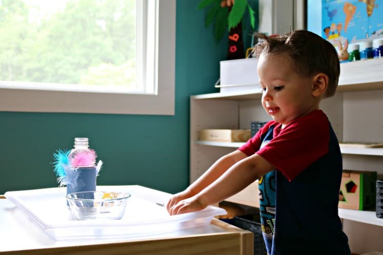 toddler boy standing near a table working on Feed the Bird activity