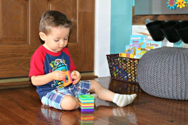 toddler boy sitting on the floor playing with magnetic tiles