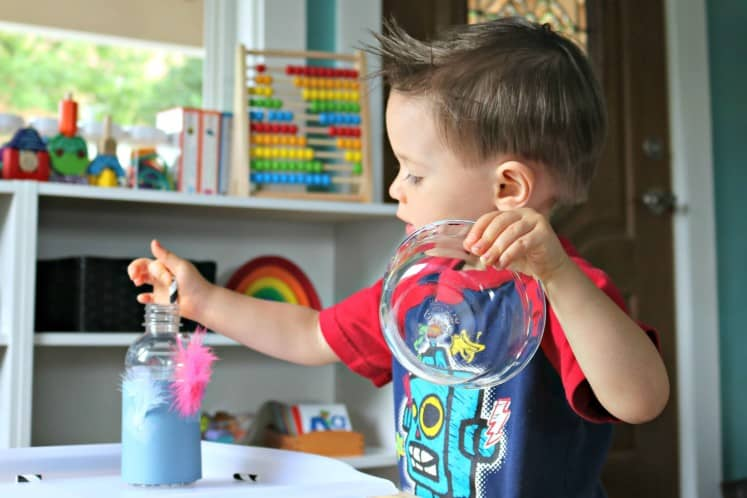 toddler boy holding clear dish and putting cut up straws in bottle decorated to look like a baby bird