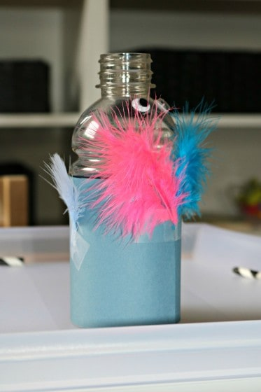 small plastic bottle decorated to look like a baby bird using feathers, cardstock and wiggle eyes