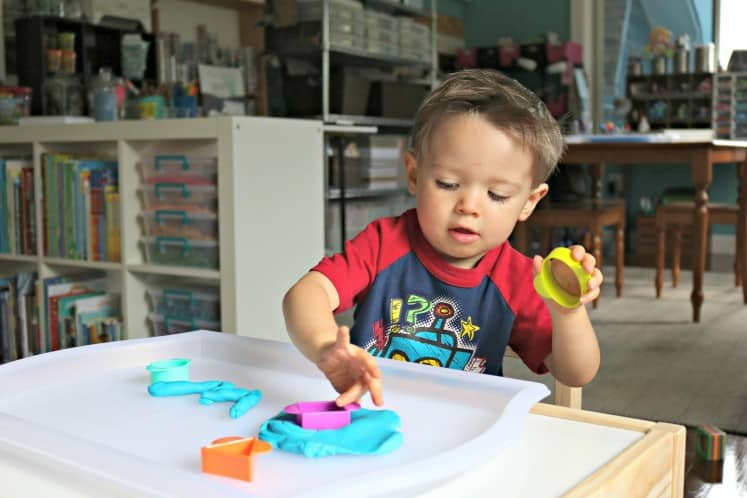 toddler boy exploring shape cookie cutters with play dough