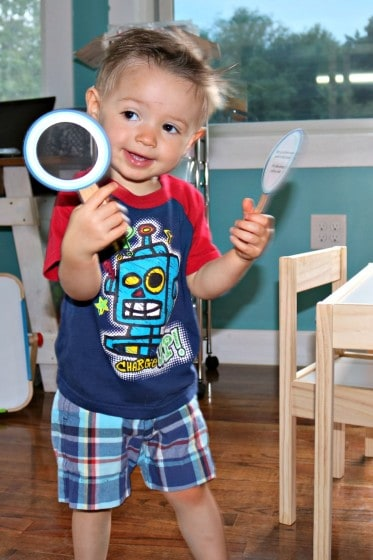 toddler boy holding two paper magnifying glasses