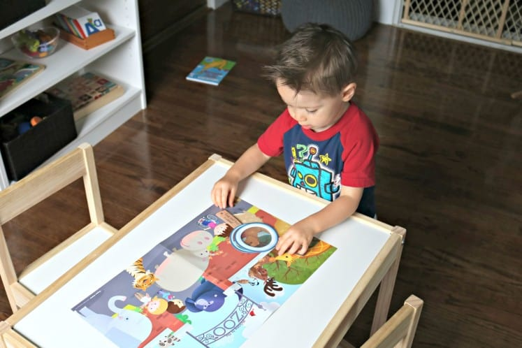 toddler boy looking at zoo theme poster on table
