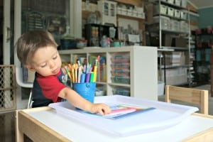 toddler boy reaching for pencil on table