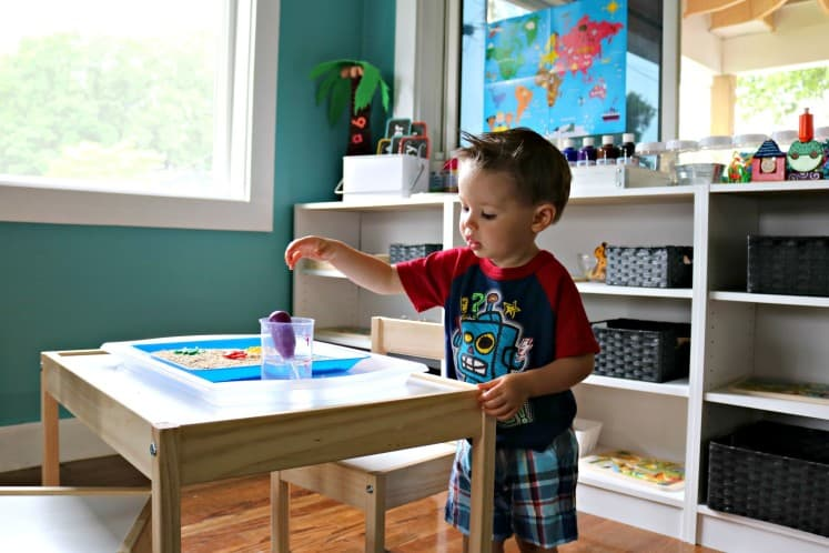 toddler boy reaching for eyedropper in clear cup