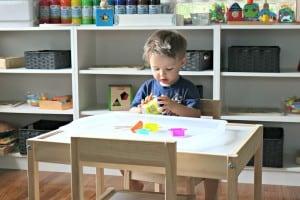 toddler sitting at a table playing with play dough and cookie cutters