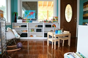 children's play space with toys neatly organized on shelves, rocking chair and children's table and chairs