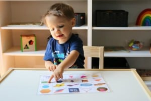 toddler boy pointing to pictures on a piece of paper