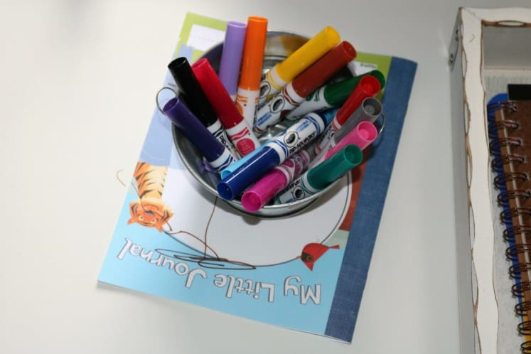 bucket of markers on top of journal
