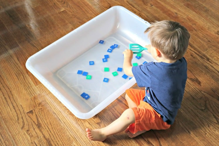 toddler boy using a spatula to scoop letter tiles from a tub of water