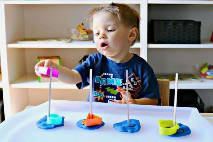 toddler boy matching shape cookie cutters to corresponding play dough impressions