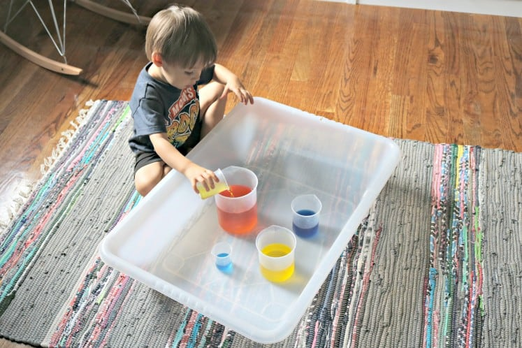 toddler exploring color mixing with plastic beakers full of colored water