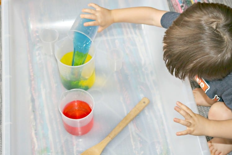 toddler pouring a beaker of blue water into one with yellow water