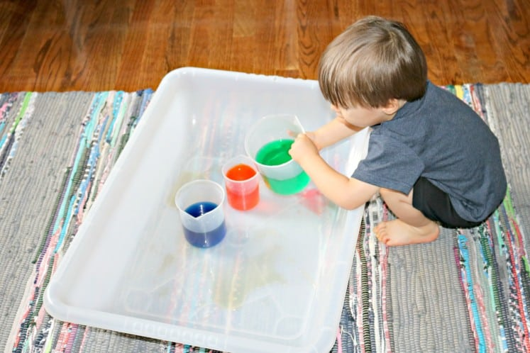 toddler pouring beaker of green water into one with red water